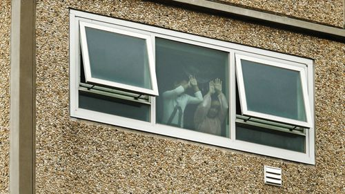 Children press their hand and faces to the window in one of the locked down public housing units.