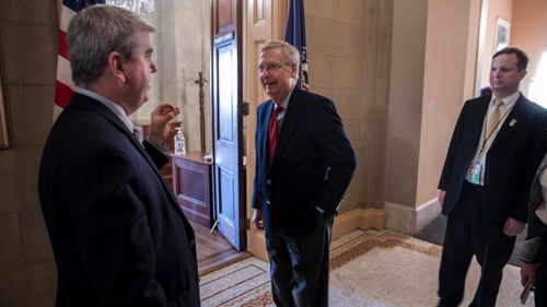 Senate Majority Leader Mitch McConnell (centre) outside his office as the Senate works on ending shutdown. (AAP)