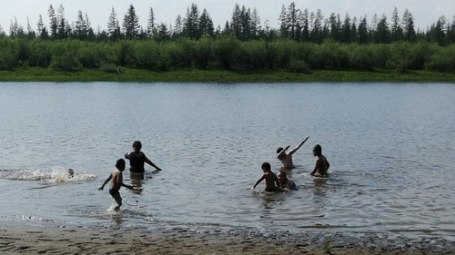 In this handout photo provided by Olga Burtseva, children play in the Krugloe lake outside Verkhoyansk, the Sakha Republic, about 4660 kilometers (2900 miles) northeast of Moscow, Russia, Sunday, June 21, 2020.