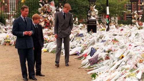 Prince Charlies, Prince William and Prince Harry, view the sea of floral tributes to Diana Kensington Palace in 1997. (AAP)