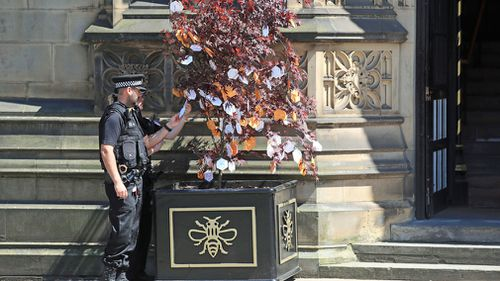 Police officers read messages left on a 'Tree of Hope'. (AAP)