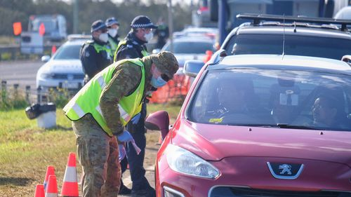 Members of the ADF and Victoria Police work together at a vehicle checkpoint.