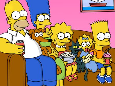 The Simpsons family sit on their couch