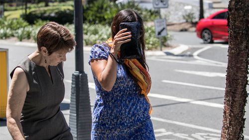 Maria Playford (right) leaves the Brisbane Supreme Court with a friend after the sentencing of her former husband. (Image: AAP)