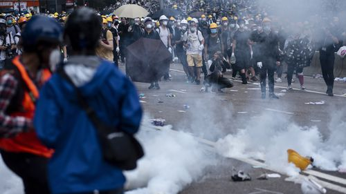 Protesters try to retreat through tear gas smoke canisters away from them during the demonstration.
