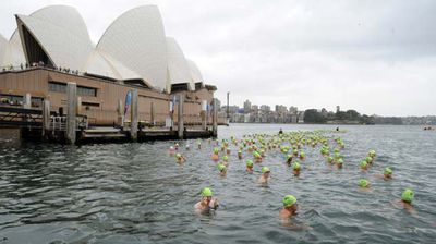 Dozens of Sydneysiders joined the annual harbour swimming race on a gloomy day. (AAP)