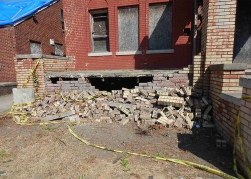 Bricks lie scattered from the collapsed side of his home.