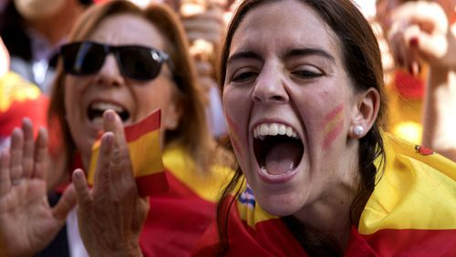 Demonstrators shout slogans as thousands of people march to protest the Catalan government's push for secession from the rest of Spain in downtown Barcelona. (AAP)