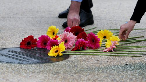 Family and community members lay flowers and pay their respects at this year's Bali Bombings memorial.