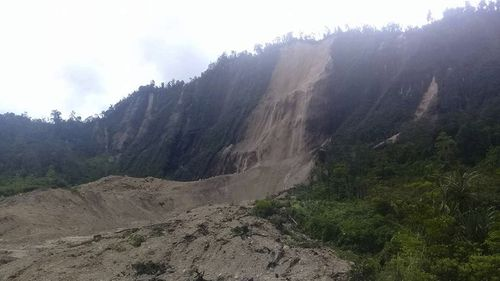 In this Monday, Feb. 26, 2018, photo, debris from a massive landslide from Monday's earthquake covers an area in Tabubil township, Papua New Guinea. The 7.5 magnitude powerful earthquake in Papua New Guinea is hindering efforts to assess the destruction, although officials fear dozens of people may have been injured or killed. (Luke Purre via AP
