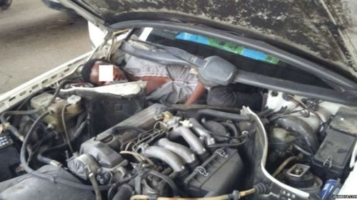 West African migrant found hiding behind car engine