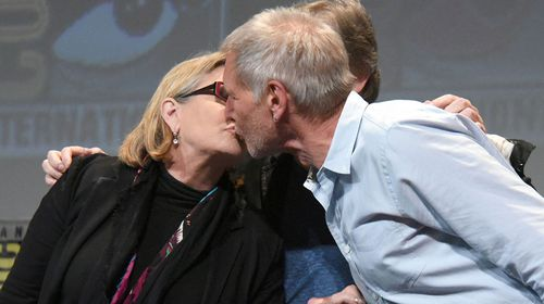 Fisher and Ford share a kiss in front of crowds at Comic-Con International. (Getty)