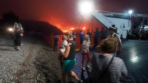 People embark a ferry during an evacuation from Kochyli beach as wildfire approaches near Limni village on the island of Evia.