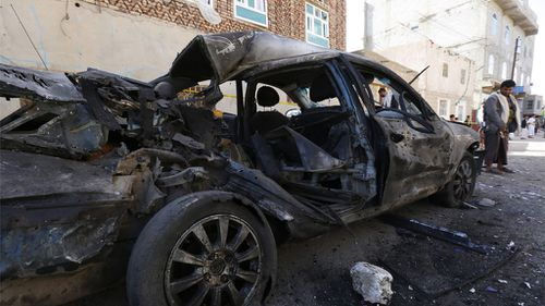 A Yemeni stands beside a car destroyed in the suicide attack. (AAP)