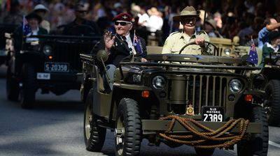 An elderly veteran is driven in a vintage army vehicle during an ANZAC Day parade in Brisbane. (AAP)