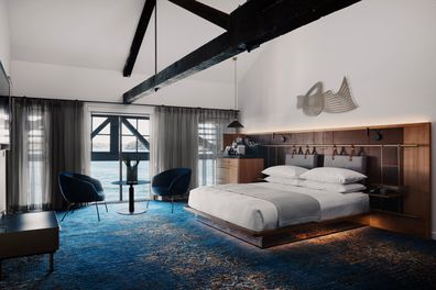 A mirrored bed base coupled with accent lighting makes the bed almost appear  to float on the water-like carpet.