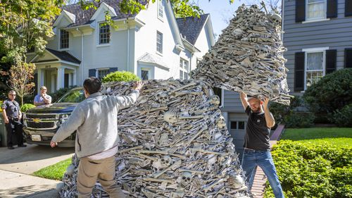 As police and Secret Service look on, a twelve-foot tall pile of artificial human bones at a vaccine equity demonstration is dismantled at the home, left, of White House Chief of Staff Ron Klain.