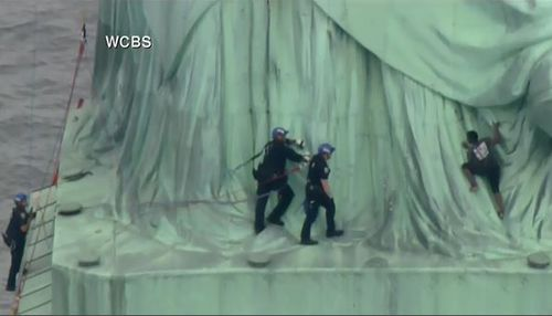 Police officers have closed in on the woman who climbed the Statue of Liberty. Picture: Supplied