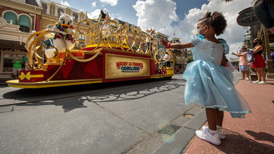 "Guests wave as the ""Mickey and Friends Cavalcade"" passes by on Main Street, USA, at Magic Kingdom's July 11, 2020, reopening."