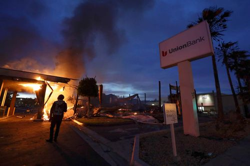 San Diego County sheriff officers stand guard in front of a burning bank building.