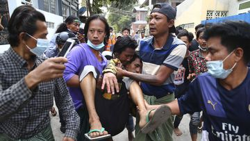 A man is carried after police dispersed protesters in Mandalay, Myanmar on Saturday, Feb. 20, 2021