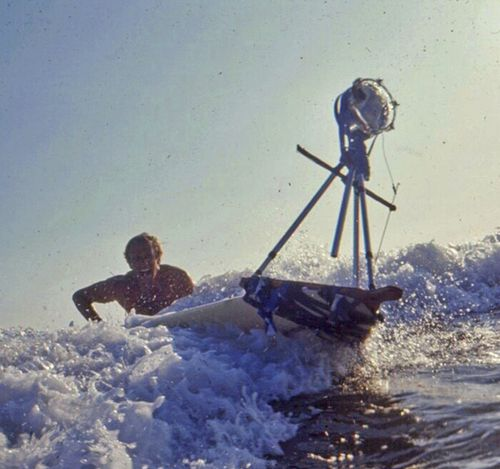 In this January, 1963 photo provided by Bruce Brown Films, filmmaker Bruce Brown tries to control a surfboard with a mounted camera mounted while making one of his many surfing movies. (AAP)