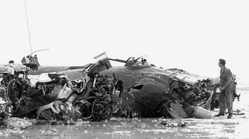 In this 1944 photo provided by the U.S. Army, a member of the military stands near a B-24 bomber that crashed shortly after takeoff from an airfield on the Tarawa atoll in the Gilbert Islands in the Pacific Ocean during World War II.