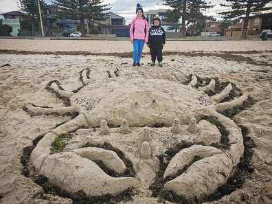 The Devoil family sculpt a giant crab in the sand at a Melbourne beach to cheer up locals in lockdown