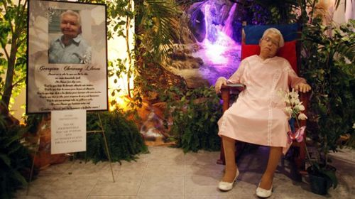 Grandma sits in rocking chair at her own funeral