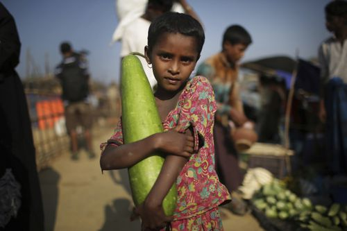 A Rohingya Muslim girl carries a vegetable from the market on the outskirts of Kutupalong refugee camp. (AAP)