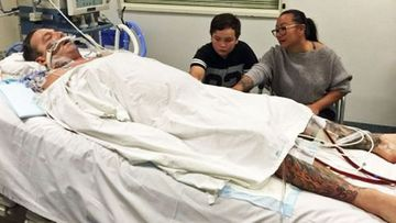 Russell Marsh in hospital with his son Ronan and wife Helen.
