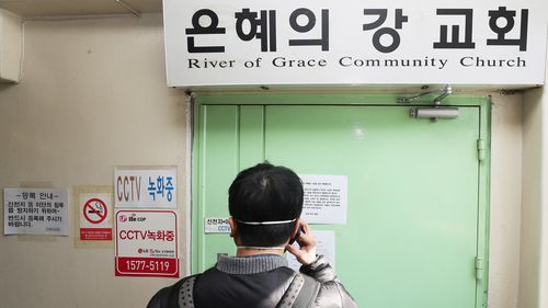 A man takes a photograph at the gate to the temporarily closed River of Grace Community Church, which will be shut until March 22.