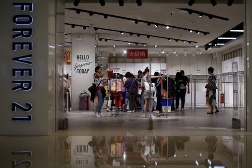 "Women select clothing at an American fast fashion retailer ""Forever 21"" which is offering clearance discounts at a shopping mall after it pulled out from China's market, in Beijing, Tuesday, May 7, 2019. (AP Photo/Andy Wong)"
