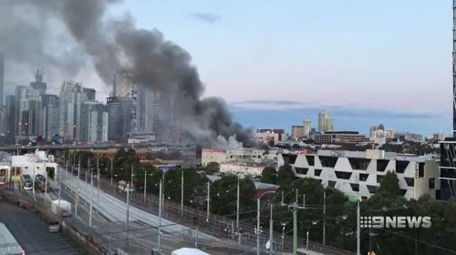 Multiple fire crews are battling to control a factory fire that has caused thick black smoke to billow out over the Melbourne CBD.