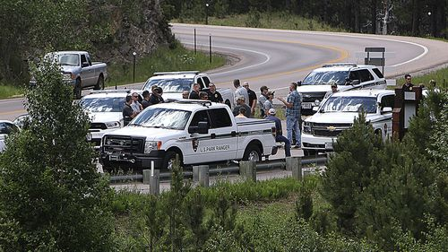 Law enforcement officers meet Thursday, July 2, 2020, at the site near Horse Thief Lake where traffic trying to enter the Mount Rushmore National Memorial, S.D., will be stopped and screened