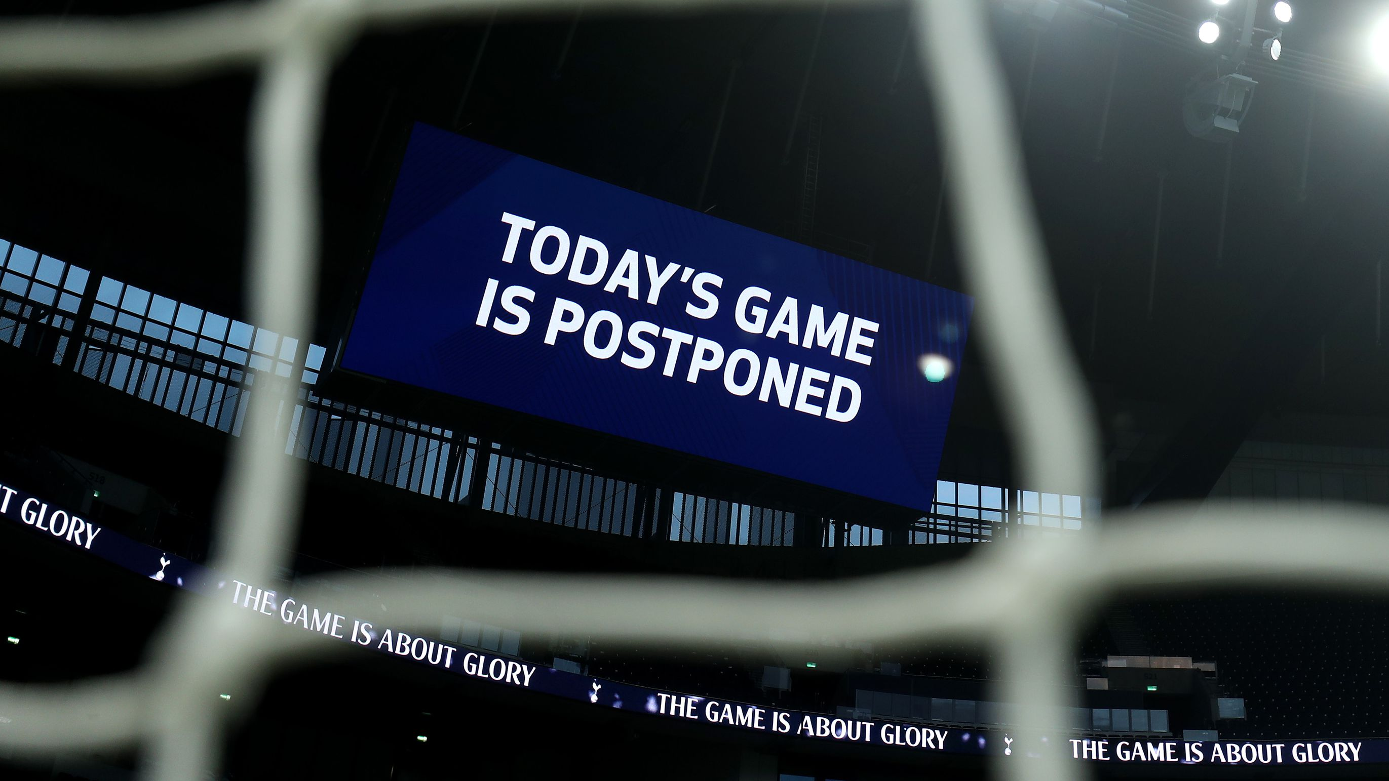 A board inside the stadium displays 'Today's Game is Postponed.'