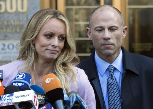 """Adult film actress Stormy Daniels, left, stands with her lawyer Michael Avenatti as she speaks outside federal court, in New York. The Justice Department says Avenatti, made """"misrepresentations"""" in a bankruptcy case involving his former law firm that owes more than $440,000 in unpaid federal taxes. Avenatti said Wednesday, July 4, 2018, he doesn't owe any money personally and called the court filing """"politically motivated."""" (AP Photo/Mary Altaffer, File)"""