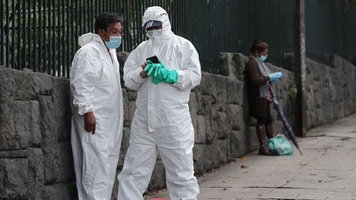 Men wearing biological safety suits stand outside Carlos Andrade Marin Hospital in Quito, Ecuador.