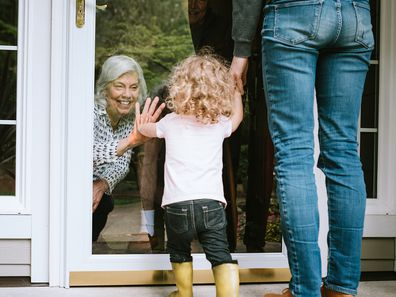 Grandmother greets grandchildren through glass