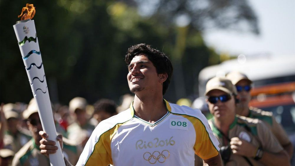 Former surfing world champ Gabriel Medina carries the Olympic torch. (Supplied)