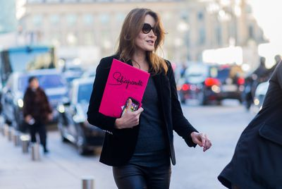 France's former First Lady Carla Bruni clutches a Schiaparelli invite in the shade of the season.