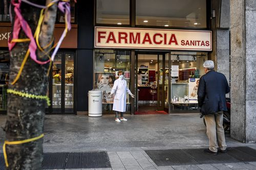 A pharmacist wears a mask as she speaks to a man keeping his distance, outside a pharmacy in Milan, Italy, Wednesday, March 11, 2020. Picture: Claudio Furlan