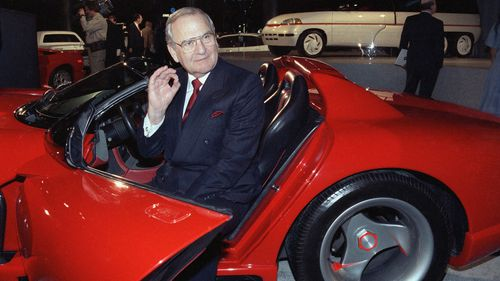 Chrysler Corporation Chairman Lee Iacocca sits in a 1990 Dodge Viper sports car.