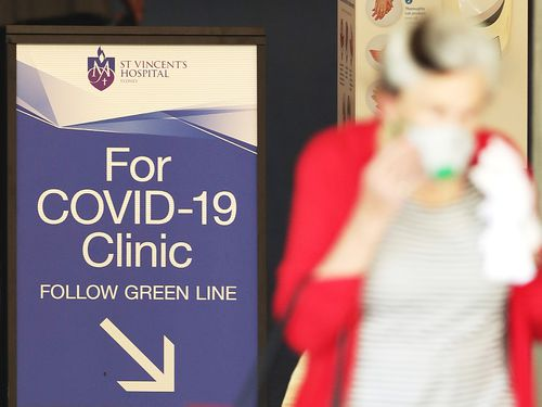 A woman passes a sign for a COVID-19 Clinic as she exits St Vincent's hospital in Sydney Australia