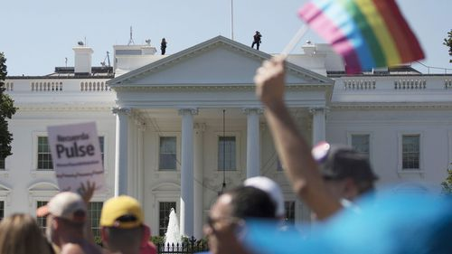 Protests outside the White House after the US President announced the ban in July. Image: AP