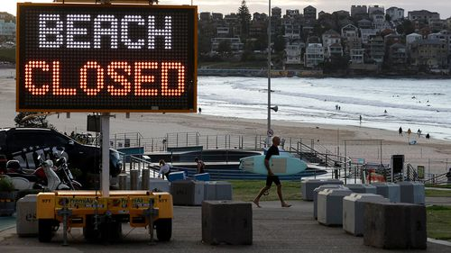 This April photo shows a sign at Bondi Beach as a surfer arrives at the Sydney beach.