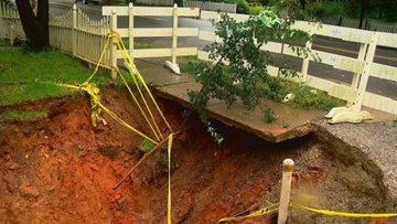 A neighbour is worried about a sinkhole that is growing bigger next to his property.