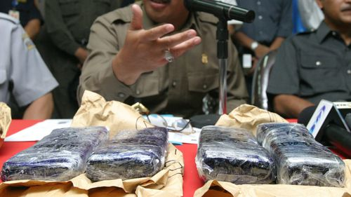 Chairman of Indonesian National Drug bureau Makbul Padmanegara shows the six kilograms of smuggled heroin. (AAP)