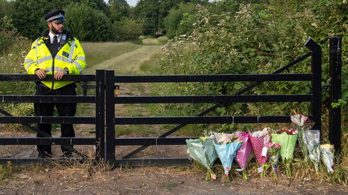 Flower tributes at an entrance to Fryent Country Park, in north London, where a murder investigation has been launched following the deaths of two sisters, Monday June 8, 2020. (Dominic Lipinski/PA via AP)