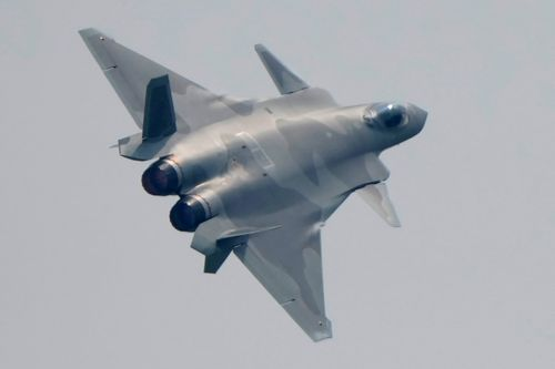 A J-20 stealth fighter jet screams above crowds at the 2021 Airshow China.
